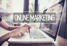 Geschäftshand, die auf einer Laptoptastatur mit Online-Marketing schreibt Stockfoto