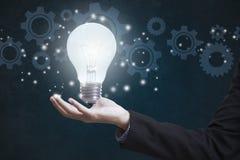 Geschäftshand, die Birne des elektrischen Lichtes mit Gangrädern hält lizenzfreies stockbild