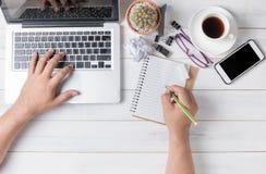 Geschäftshandmann, der Computer verwendet und auf leeres Notizbuch schreibt Stockfotos