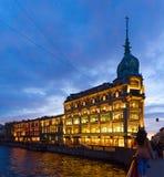 Geschäftshaus Esders und Scheefhals in der Abendbeleuchtung, Damm von Fluss Moika, St Petersburg, Russland Lizenzfreies Stockbild
