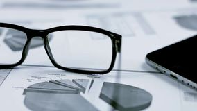 Geschäftshintergrund mit Grafiken und Gläsern stock footage