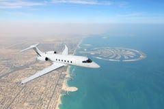 Geschäftsjet-Flugzeug, das über Dubai-Stadt- und -seeküstenlinie fliegt Stockfotografie