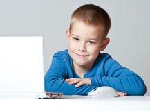 Geschäftsjungenlächeln, das unter Verwendung des Laptops arbeitet Stockfoto