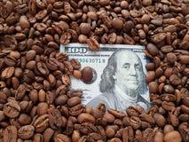 Geschäftskaffee, 100 Dollarschein mit Kaffeebohnehintergrund Lizenzfreie Stockfotografie
