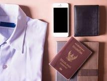 Geschäftskleidung stellte vom weißen intelligenten Telefon, von der hinteren Geldbörse und vom Notizbuch mit Thailand-Pass in den Stockfoto