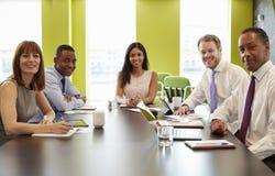 Geschäftskollegen bei einer informellen Sitzung schauen zur Kamera lizenzfreie stockfotografie