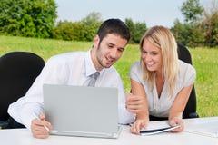 Geschäftskollegen in der Natur mit Laptoplächeln Stockbilder