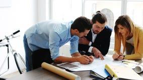 Geschäftskollegen, die über Plan sich besprechen stock footage
