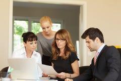 Geschäftskollegen, die an einem Laptop arbeiten Lizenzfreie Stockbilder