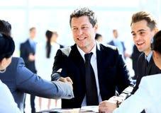 Geschäftskollegen, die an einem Tisch während einer Sitzung mit zwei mal sitzen Lizenzfreie Stockbilder