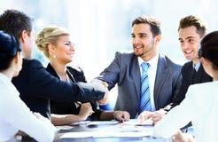 Geschäftskollegen, die an einem Tisch während einer Sitzung sitzen Lizenzfreie Stockfotografie