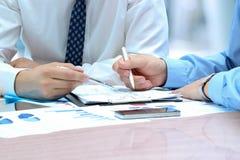 Geschäftskollegen, die Finanzzahlen auf Diagramme bearbeiten und analysieren Lizenzfreies Stockbild