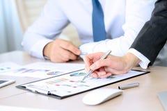 Geschäftskollegen, die Finanzzahlen auf Diagramme bearbeiten und analysieren Stockbilder