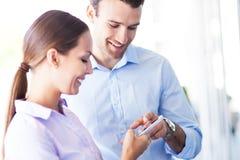 Geschäftskollegen, die Handy betrachten stockbilder