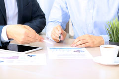 Geschäftskollegen, die zusammenarbeiten und Finanzzahlen auf Diagramme analysieren Stockfoto