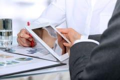 Geschäftskollegen, die zusammenarbeiten und Finanzzahlen auf Diagramme analysieren Stockfotos