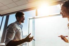 Geschäftskollegen im Büro Arbeit besprechend Lizenzfreie Stockfotografie
