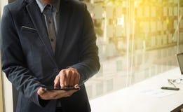 Geschäftskonzept, Bild des jungen Geschäftsmannes unter Verwendung des teblet am wor Stockfotografie