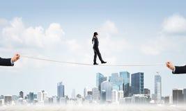 Geschäftskonzept der Risikounterstützung und -hilfe mit dem Mann, der auf Seil balanciert Stockbilder