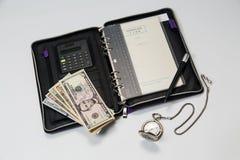 Geschäftskonzept des Organisators, der Dollar und der Uhr Stockfotografie