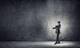 Geschäftskonzept des Risikos mit tragender Augenbinde des Geschäftsmannes im leeren konkreten Raum Stockfotos
