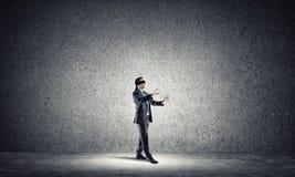 Geschäftskonzept des Risikos mit tragender Augenbinde des Geschäftsmannes im leeren konkreten Raum Lizenzfreie Stockfotos