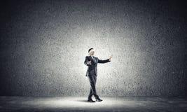 Geschäftskonzept des Risikos mit tragender Augenbinde des Geschäftsmannes im leeren konkreten Raum Stockfotografie