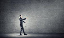Geschäftskonzept des Risikos mit tragender Augenbinde des Geschäftsmannes im leeren konkreten Raum Lizenzfreie Stockbilder