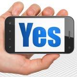 Geschäftskonzept: Hand, die Smartphone mit ja auf Anzeige hält Lizenzfreie Stockbilder