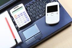Geschäftskonzept mit einem blauen Notizbuch, weißer Taschenrechner, roter Stift Lizenzfreie Stockfotos