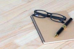 Geschäftskonzept, -stift, -gläser und -notizbuch auf hölzernem Bürovorsprung stockbilder