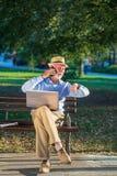 Geschäftskorrespondenz Fokussierter reifer Geschäftsmann unter Verwendung des Laptops beim Sitzen im Park stockfotografie
