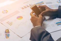 Geschäftsleute übergeben das Arbeiten mit einem Smartphone auf weißem Tabellenhintergrund Stockfoto