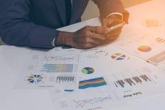 Geschäftsleute übergeben das Arbeiten mit einem Smartphone auf weißem Tabellenhintergrund Stockfotografie