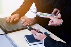 Geschäftsleute überprüfen das Finanzdiagramm im Büro Stockbilder