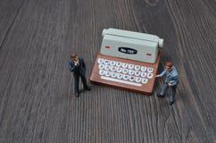 Geschäftsleute auf Stadium mit Schreibmaschine Lizenzfreie Stockfotografie