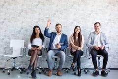 Geschäftsleute bei einer Konferenz im Büro mit Telefonen in den Händen Lizenzfreie Stockbilder