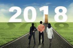 Geschäftsleute betrachten Tür und Nr. 2018 stockbild