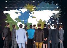 Geschäftsleute in der Gruppe, die bunte Karte mit Farbe betrachtet, spritzen auf Wandhintergrund Lizenzfreie Stockfotografie