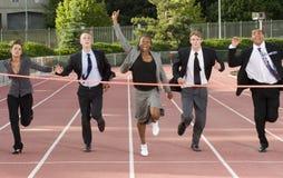 Geschäftsleute, die über die Ziellinie laufen Lizenzfreies Stockfoto