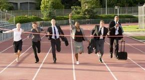 Geschäftsleute, die über die Ziellinie laufen Stockfotos