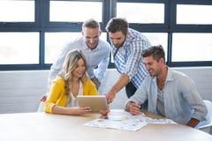 Geschäftsleute, die über Tablet-Computer sich besprechen stockbilder