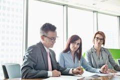Geschäftsleute, die auf Bücher am Konferenztische schreiben lizenzfreies stockfoto