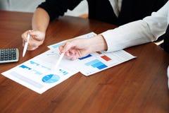 Geschäftsleute, die auf Diagramme zeigen Lizenzfreie Stockbilder