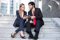 Geschäftsleute, die auf einem Treppenhaus sitzen Lizenzfreies Stockbild