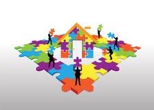 Geschäftsleute, die auf Puzzlegebäudehaus stehen Stockbilder