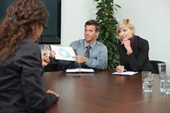 Geschäftsleute, die auf Sitzung sitzen Stockbild