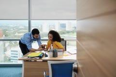 Geschäftsleute, die in Büro-aufpassenden Videobildern auf Smartphone lachen stockfotos