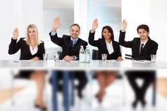 Geschäftsleute, die bei der Sitzung wählen Lizenzfreies Stockfoto