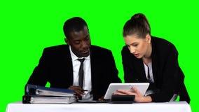 Geschäftsleute, die beim Betrachten von Diagrammen im Laptop in einem Büro zusammenarbeiten Grüner Bildschirm stock footage